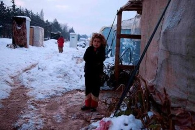 Cold day in a refugee camp. Eight-year-old Syrian refugee Mariha stands outside her temporary home in Lebanon. ...