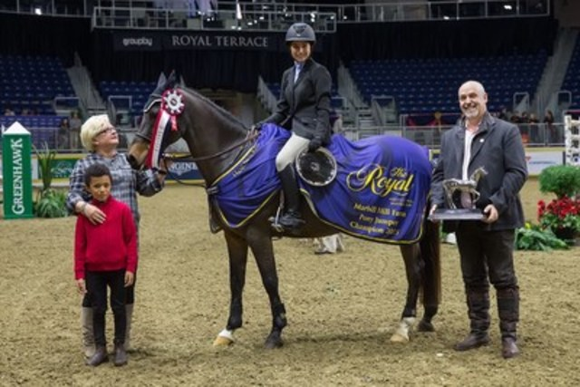 Raphaelle Ferreira of Prevost, QC, accepts the Pony Jumper Championship from Marion Cunningham and William Tilford of Marbill Hill Farm after a second-place finish on Sunday at the Royal Horse Show®. (CNW Group/Royal Agricultural Winter Fair)