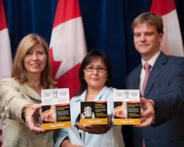 L'honorable Leona Aglukkaq (au centre), ministre de la Santé, a annoncé qu'à compter d'aujourd'hui, les détaillants ne doivent vendre que des paquets de cigarettes et de petits cigares affichant les nouvelles mises en garde agrandies. La ministre Aglukkaq était accompagnée de Chris Alexander (à droite), député d'Ajax-Pickering et de Bobbe Wood (à gauche), présidente de la Fondation des maladies du cœur. (Groupe CNW/Santé Canada)