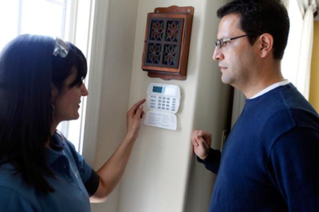 Nicole Marks, technicienne certifiée pour le service Sécurité résidentielle évoluée, explique le fonctionnement du panneau de commande à Carlos Barbosa (Groupe CNW/BELL ALIANT INC. - FRANCAIS)