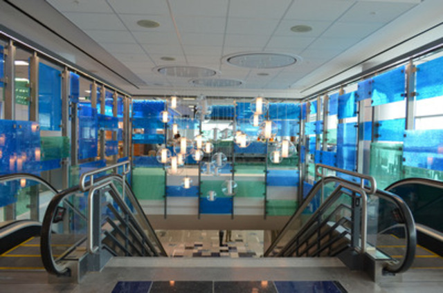 An architectural representation of Niagara Falls using elements like blue-hued floor tiles, acrylic wall panels textured to suggest water, and chandeliers that resemble dancing bubbles surrounds the main escalator in the Terminal 3 pier. (CNW Group/Greater Toronto Airports Authority)