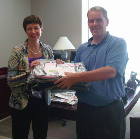 President and CEO, Karen Sheriff accepts her adopted backpacks from Backpacks for Kids volunteer and employee, David Lennard. (CNW Group/BELL ALIANT INC.)