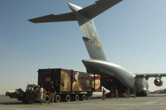 Arrivée de la remorque Tim Hortons à bord d'un avion militaire à la base d'opérations des Forces canadiennes à Kandahar, en Afghanistan, avant son inauguration à la fête du Canada, en 2006. (Groupe CNW/Tim Hortons Inc.)