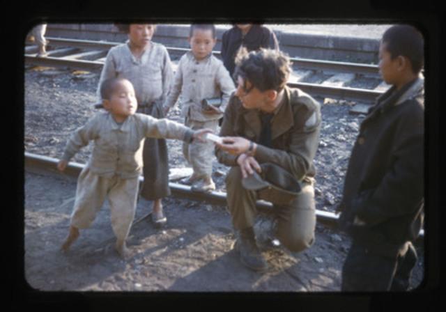 Cette photo de 1953 montre un artilleur canadien offrant des bonbons à un jeune garçon coréen, aux installations ferroviaires de Tokchon, en Corée du Sud. (Groupe CNW/Musée canadien de la guerre)