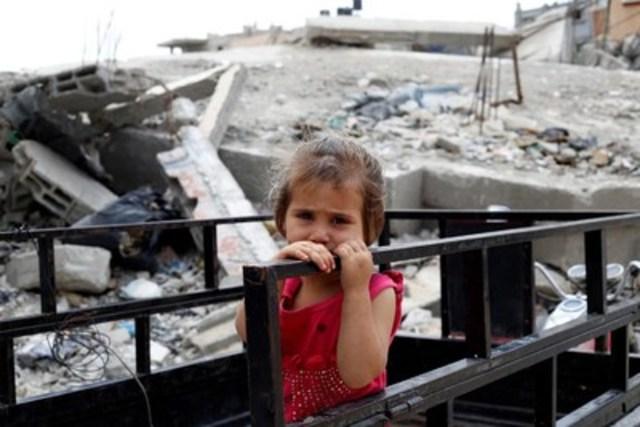 Une jeune fille se tient à une rampe à l''extérieur de sa demeure, partiellement détruite dans la bande de Gaza. Elle est parmi les 60 enfants et 20 adultes de la même famille vivant dans cette maison qui a subi un bombardement aérien l''an dernier. Les décombres et débris du domicile - –visibles derrière elle –- sont devenus le terrain de jeux des enfants. © UNICEF/UNI188295/El Baba (Groupe CNW/UNICEF Canada)
