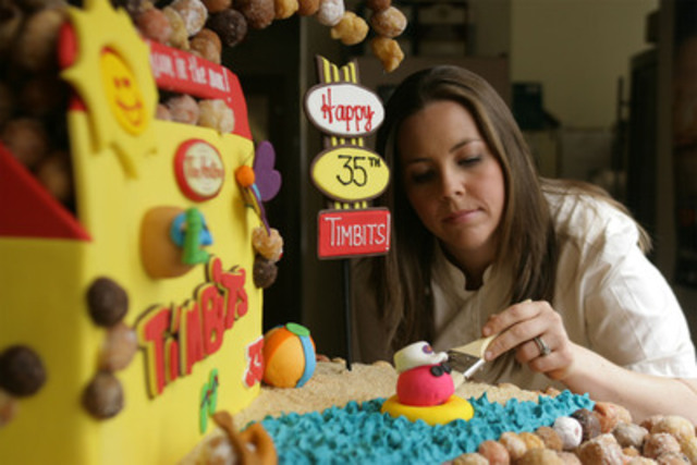 Chef Andrea Nicholson, rising culinary star and Top Chef Canada contestant, puts the finishing touches on the Tim Hortons Timbits 35th birthday cake. Standing close to four feet tall, Nicholson created the cake using more than 1,500 Timbits. (CNW Group/Tim Hortons Inc.)