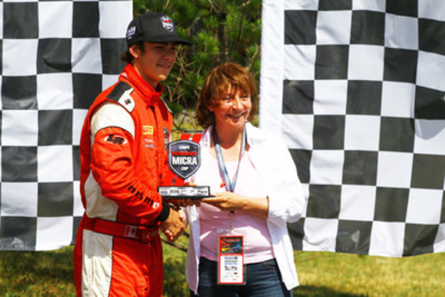 Mrs. Joann Villeneuve presents the trophy to the winner of the second race, Olivier Bédard. (CNW Group/Nissan Canada Inc.)