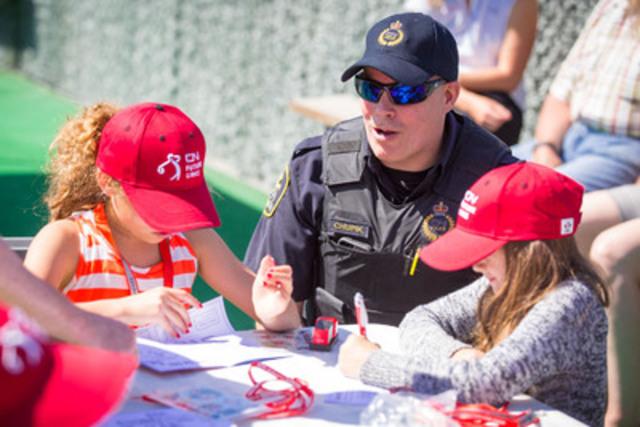 Mark Chupik, constable à la CN Police, parle de sécurité ferroviaire aux enfants au terrain de golf Mount Paul, à Kamloops (C.-B.). Le CN a adopté 15 écoles de la région de Kamloops dans le cadre de la Tournée des collectivités du programme Premiers élans CN 2015. (Groupe CNW/La Compagnie des chemins de fer nationaux du Canada)
