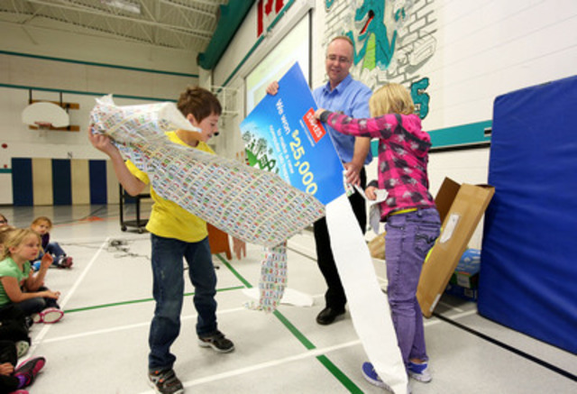 Dave Friesen, General Manager of the Staples Brandon, MB location, has some help from Oak Lake Community School students to reveal that they won one of Staples Canada's Recycle for Education $25,000 prizes during an assembly at the school. (CNW Group/Staples Canada Inc.)