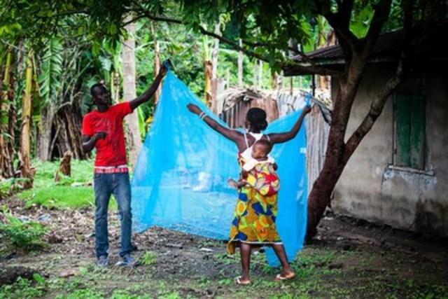 En Sierra Leone, dans le district de Port Loko, un jeune homme aide une femme, qui transporte un bébé sur son dos, tandis qu''elle étend à l''ombre pour 24 heures une moustiquaire pour le lit imprégnée d''insecticide longue durée. Les nouvelles moustiquaires imprégnées d''insecticide doivent rester à l''air libre pendant 24 heures avant d''être en contact avec la peau d''êtres humains. (Groupe CNW/UNICEF Canada)