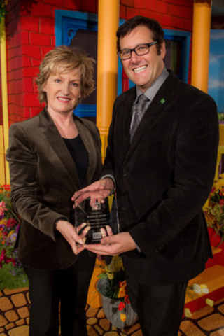 Lisa de Wilde, Chief Executive Officer of TVO, presents the TVO Caring Corporate Partner Award to Alan Convery, TD Bank Group National Manager Community Relations, on the set of TVO's Gisèle's Big Backyard. (CNW Group/TVO)
