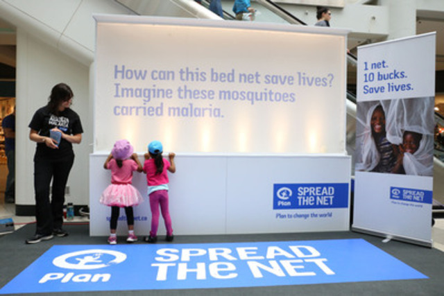 Children look at an installation of more than 12,000 live mosquitoes at the Toronto Eaton Centre for Plan Canada's Spread the Net campaign, a global movement to end malaria. To learn more visit spreadthenet.ca. Photo credit: Angie Torres-Ramos/Plan Canada (CNW Group/Plan Canada)