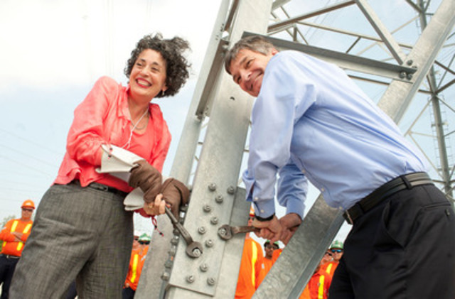 Minister Chris Bentley and Hydro One President and CEO, Laura Formusa tighten the last bolt on the final tower in the Bruce to Milton transmission project. (CNW Group/Hydro One Inc.)