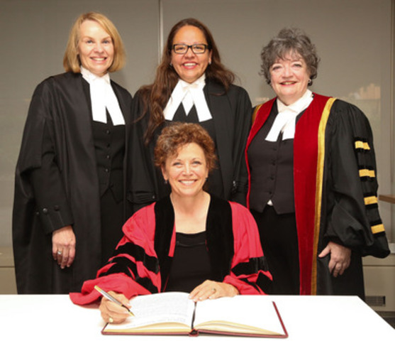 The Law Society of Upper Canada presented an honorary LLD to Jean Teillet, IPC (seated), at the June 26th Call to the Bar morning ceremony in Toronto. Teillet is congratulated by Law Society Treasurer Janet E. Minor (right), Bencher Dianne Corbiere (middle) and Justice Katherine van Rensburg, as she signs the LLD register. (CNW Group/The Law Society of Upper Canada)