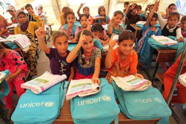 Students raise their hands to answer a teacher's question during summer catch-up classes at the UNICEF tent  ...