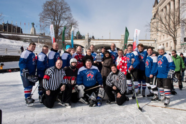 Minister Steven Blaney, captain of the Parliamentary team, stands behind Senator Yonah Martin and Korean Ambassador Hee-yong Cho, who hold the Imjin River Memorial Cup. Parliamentarians and military members played a friendly game of pond hockey on the Rideau Canal in honour of Canadian Korean War Veterans.(CNW Group/Veterans Affairs Canada)