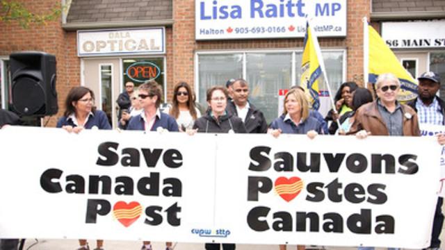 Des représentantes et représentants du Syndicat des travailleurs et travailleuses des postes (STTP) et d'autres groupes concernés manifestent devant le bureau de la ministre Lisa Raitt, à Milton.