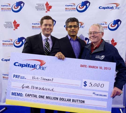 Clinton Braganza from Capital One Canada hands over a $5,000 cheque to Bob Stewart of Longbow Lake, ON for his final throw in the Million Dollar Button contest. (CNW Group/Capital One Services, Inc.)