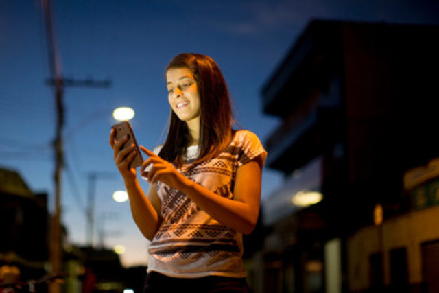 Winny Moreira, 17, uses her mobile phone on a street in Taiobeiras, Brazil. UNICEF is launching two new mobile ...