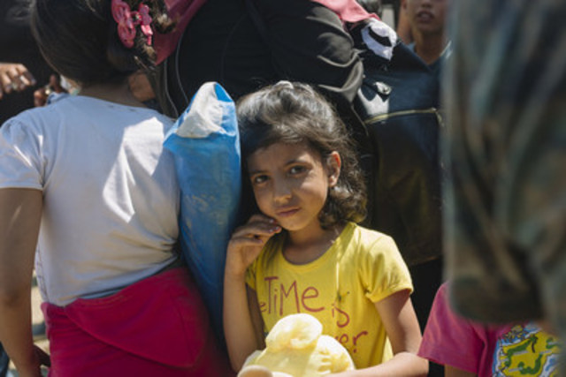 A young girls stands with other children and adults at a reception centre in Gevgelija in the former Yugoslav Republic of Macedonia after crossing the border from Idomeni in Greece. Many are escaping conflict and insecurity in their home countries. © UNICEF/UNI195496/Klincarov (CNW Group/UNICEF Canada)