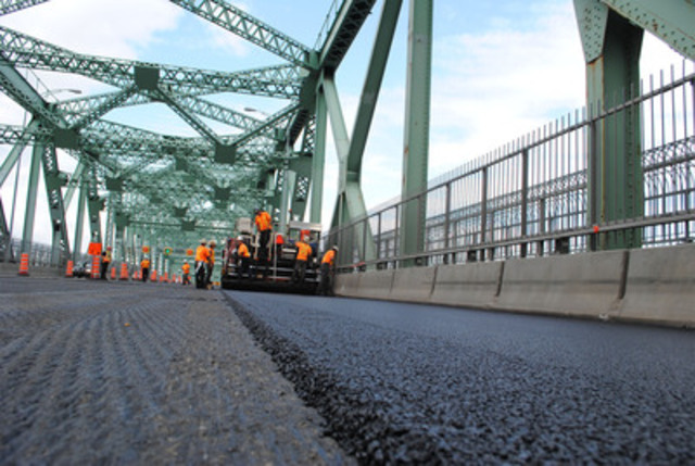Workers paving the Jacques-Cartier Bridge, which was finished in less than six days during the 2012 Construction Holiday. They managed to get everything done despite a violent thunderstorm striking Montreal on July 23. (CNW Group/The Jacques Cartier and Champlain Bridges Incorporated)