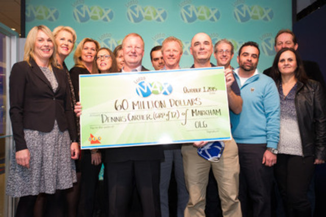 Twelve Toronto area co-workers are presented a record high $60 million LOTTO MAX cheque from OLG's Vice President of Lottery Marketing and Sales Wendy Montgomery at the OLG Prize Centre in Toronto, ON. (CNW Group/OLG Winners)