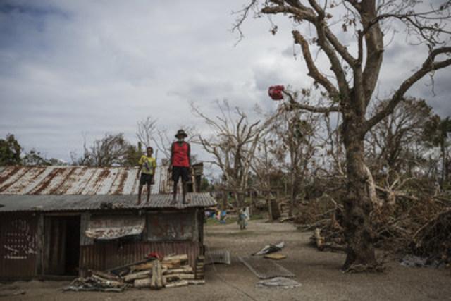 Un enfant et un homme âgé se tiennent debout sur le toit d'un bâtiment endommagé à Vanuatu après le passage du cyclone Pam en mars 2015. La tempête de catégorie 5 a endommagé les infrastructures et perturbé les services essentiels, mettant en danger la santé, la sécurité et l'éducation des enfants. (Groupe CNW/UNICEF Canada)