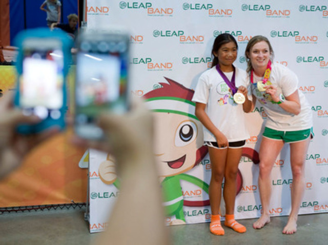 Rosie MacLennan, Olympic gold medalist and World Trampoline champion, poses for a photograph with a girl during the LeapFrog LeapBand launch event in Toronto on Wednesday, August 27, 2014. (CNW Group/LeapFrog Canada)