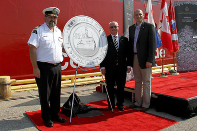 Assistant Commissioner of the Canadian Coast Guard Wade E. Spurrell, Royal Canadian Mint Chair James B. Love and MP Jeff Watson (Essex) unveil a $20 fine silver collector coin celebrating 50 years of the Canadian Coast Guard at the Government Wharf in Sarnia, Ontario (July 13, 2012) . (CNW Group/Royal Canadian Mint)