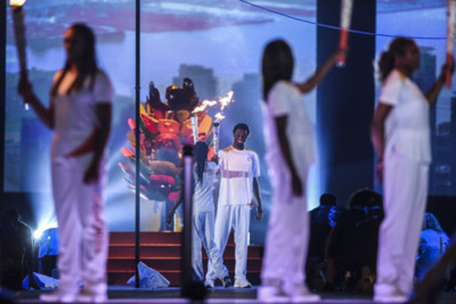The TORONTO 2015 Pan Am Games Opening Ceremony, produced by Cirque du Soleil, saw the passing of the Pan Am flame from one generation to the next, as Marita Payne-Wiggins, a member of the 1984 Los Angeles Olympic Games silver-medal-winning Canadian 4 x 400-metre relay team, passes the flame to her son, NBA star Andrew Wiggins. (CNW Group/Toronto 2015 Pan/Parapan American Games)