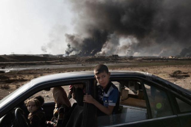 En Iraq, le 31 octobre 2016, des civils récemment déplacés à cause des combats à Mossoul s'arrêtent à un poste de contrôle à Qayyara. © UNICEF/UN040089/Romenzi (Groupe CNW/UNICEF Canada)