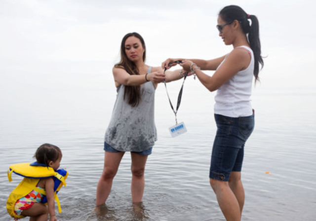 Nadia Luck remet sa carte de SURVEILLANT à une autre mère, Lala de Vera, tout en surveillant sa fille lors d'une activité de sensibilisation à l'importance de la sécurité aquatique organisée par la Société de sauvetage à la plage Woodbine, à Toronto, le mercredi 25 juin 2014. (Groupe CNW/Société de sauvetage)