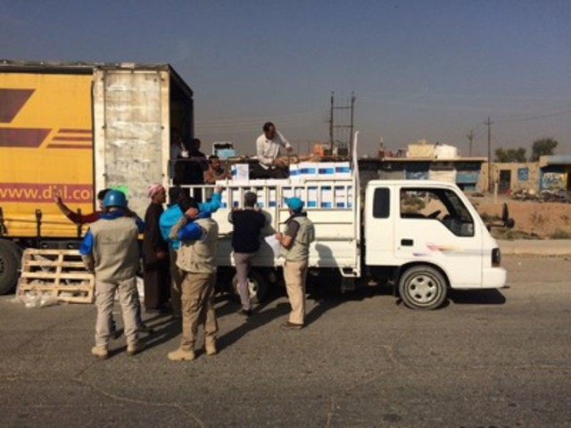 Workers load emergency supplies for 15,000 children onto a truck as part of a UNICEF-led humanitarian convoy into Mosul city. Up to 1.5 million people remain trapped inside the city, including 600,000 children. UNICEF Iraq/2016/Niles (CNW Group/UNICEF Canada)