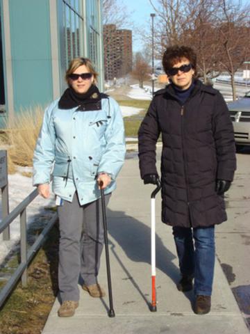 Deux dames utilisant une canne dont une utilisant une canne blanche courte qui l'identifie comme une personne ayant une déficience visuelle. (Groupe CNW/Institut Nazareth et Louis-Braille (INLB))