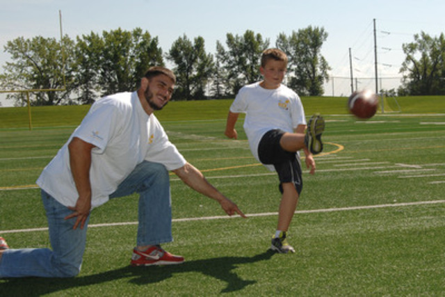 CFL player John Chick sets up 9-year-old Jack, a football fan with type 1 diabetes, for field goal victory. The defensive end, who also lives with the disease and wears an insulin pump on the field, is helping to Kick Diabetes with Sun Life Financial to raise awareness for diabetes research and management. (CNW Group/Sun Life Financial Inc.)