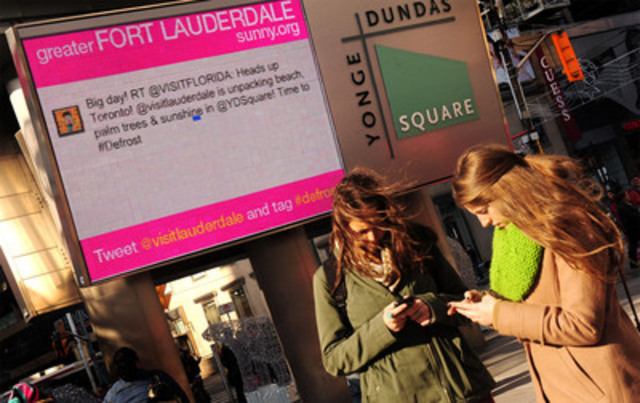 "Young Torontonians tweeting on the Greater Fort Lauderdale LIVE tweet board at Yonge - Dundas Square during the ""Defrost Your Swimsuit"" Event. (CNW Group/Greater Fort Lauderdale)"