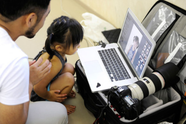 A child reviews her portrait with a volunteer photographer in Japan. (CNW Group/Shiseido Canada Inc.)