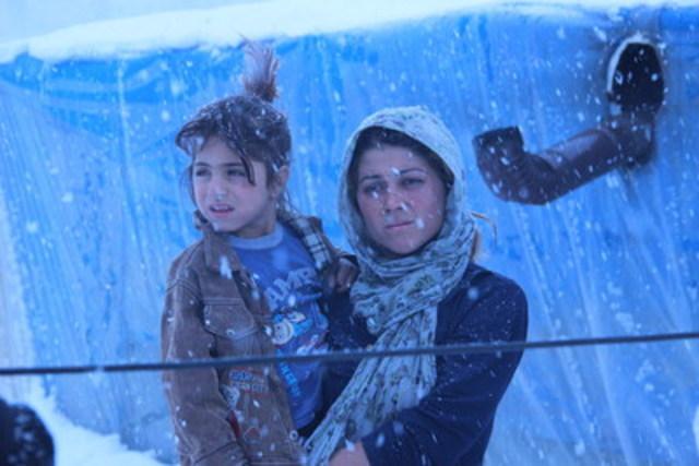 Une femme portant une fille vêtue d'une veste légère se tient dehors, près d'une tente, sous une neige abondante par une journée d'un froid mordant dans une communauté d'accueil de la vallée de Dikmen, un projet de transformation urbaine, à Ankara, la capitale. Un tuyau derrière elles envoie de la chaleur dans la tente. Les fortes chutes de neige, les tempêtes de neige et les vents violents rendent la vie quotidienne plus difficile, en particulier pour les enfants qui n'ont pas de vêtements d'hiver. (Photo crédit : © UNICEF/UNI177414/Yurtsever) (Groupe CNW/UNICEF Canada)