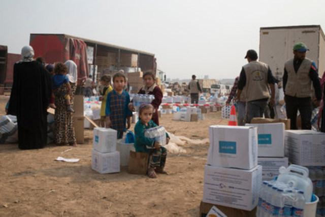 © UNICEF/UN037061/Mackenzie - De jeunes filles reçoivent de l'aide humanitaire au centre de distribution à Ibrahim Khalil, dans le nord de l'Iraq. (Groupe CNW/UNICEF Canada)