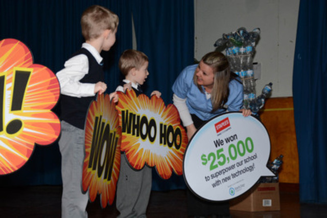 Rhonda Brothers, divisional sales manager at Staples Corner Brook, and Immaculate Heart of Mary students, Joey Lyver, left, and Thomas Randell celebrate after announcing to the school that they won $25,000 worth of new technology from Staples Canada. (The Canadian Press Images) (CNW Group/Staples Canada Inc.)