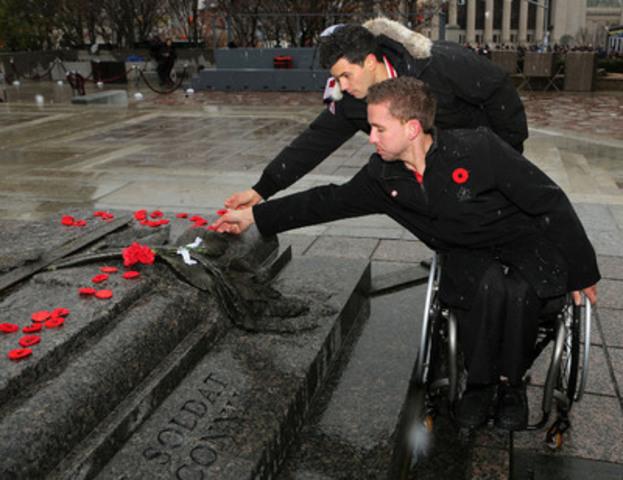 Le joueur paralympique de hockey sur luge Marc Dorion et l'olympien de canoë/kayak Michael Tayler placent des coquelicots sur la Tombe du Soldat inconnu lors de la cérémonie nationale du Jour du Souvenir le 11 novembre 2013 à Ottawa. (Groupe CNW/Comité paralympique canadien (CPC))