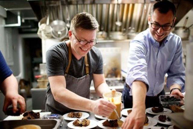 Un des chefs de l'Encan 5 ans, 5 chefs, Danny St-Pierre, propriétaire du restaurant Petite Maison, dans sa cuisine avec Richard Blain, CRHA, président du conseil d'administration de Moisson Montréal lors du souper-bénéfice de la Grande récolte pour les enfants (Groupe CNW/MOISSON MONTREAL)