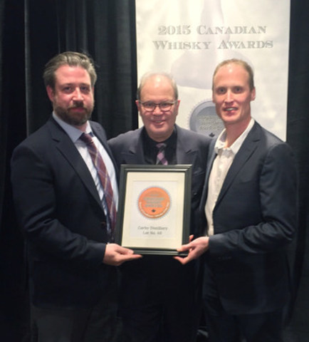 Dave Mitton, Global Canadian Whisky Ambassador, Corby Spirit and Wine (left) and Dr. Don Livermore, Master Blender, Hiram Walker & Sons (right) accept the Canadian Whisky of the Year award for Lot No. 40 from Davin de Kergommeaux, Chairman of the Judges, Canadian Whisky Awards (centre). (CNW Group/Corby Spirit and Wine Communications)