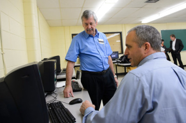 Stéphane Chaput (sitting), principal of Polyvalente des Monts, shows Denis Marcotte (standing), general manager of Bureau en Gros in Ste-Agathe-Des-Mont, the school's current computer lab. The school is being recognized for their eco initiatives and has won $25,000 worth of new technology through the 2016 Staples Canada Superpower your School Contest. (CNW Group/Staples Canada Inc.)