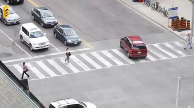 B-roll of pedestrians crossing streets, busy intersections and vehicle traffic.