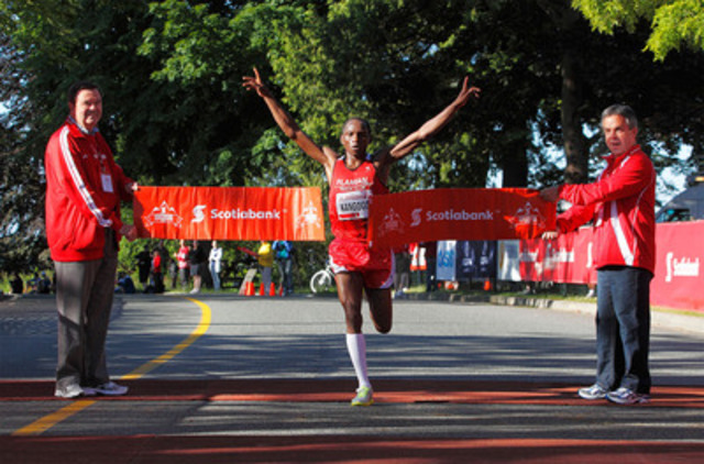 VANCOUVER, BC - JUNE 26, 2011: Winner of the men's half marathon division of the Scotiabank Vancouver 1/2 Marathon & 5K, Kip Kangogo, crosses the finish line with Rob Wilkins (R), Scotiabank Vice-President for Downtown Vancouver and Northern BC, and David Poole, Scotiabank Senior Vice-President BC & Yukon Region. (CNW Group/Scotiabank - Sponsorships & Donations)