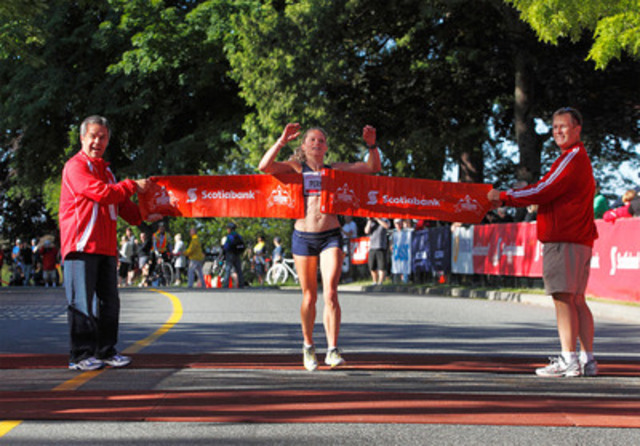 VANCOUVER, BC - JUNE 26, 2011: Winner of the women's half marathon division of the Scotiabank Vancouver 1/2 Marathon & 5K, Ruth Perkins, crosses the finish line with Rob Wilkins (L), Scotiabank Vice-President for Downtown Vancouver and Northern BC and Jeffrey Buttner, Canada Running Series. (CNW Group/Scotiabank - Sponsorships & Donations)