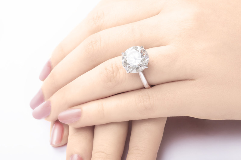 A closeup of a woman's hands and engagement ring.