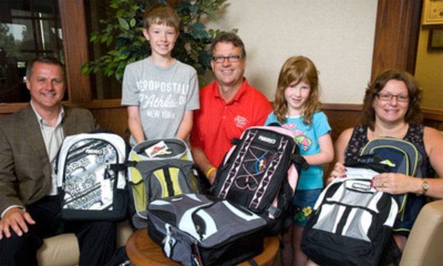 Bruce Howatt (left), vice president - PEI, Bell Aliant, joined Education and Early Childhood Development Minister Doug Currie (center) and 1st Vice President, Acadia Chapter, of the Bell Aliant Pioneers Anne Marie Ellis (right), to celebrate the successful Backpack for Kids program with Donovan Ching, (center-left), and Lindsay Ching, (center-right) children of Scott Ching, an employee of Bell Aliant. (CNW Group/BELL ALIANT INC.)