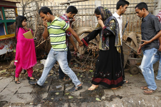 People walk past a urinating zone in Dhaka, Bangladesh. WaterAid's Overflowing Cities: The State of the World Toilets report reveals that Bangladesh ranks sixth in the world for having the greatest number of urban dwellers living without safe, private toilets-- 23 million people. (CNW Group/WaterAid Canada)